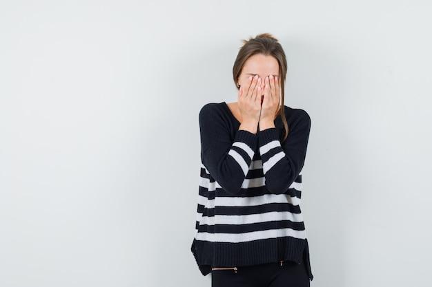 Молодая женщина в полосатом трикотажном белье и черных брюках закрывает лицо руками и выглядит измученной