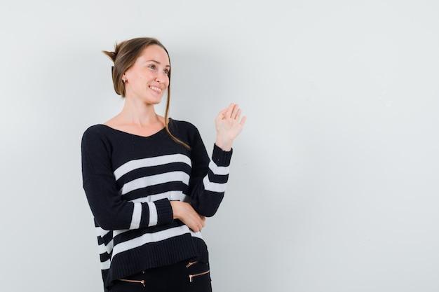 Молодая женщина в полосатом трикотажном белье и черных штанах приветствует кого-то и выглядит счастливой