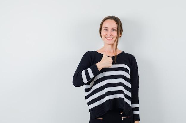 ストライプのニットと黒のズボンの若い女性は親指を上に表示し、幸せそうに見えます