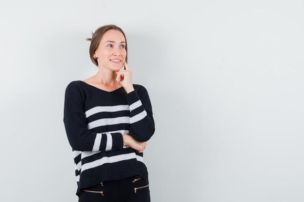 Молодая женщина в полосатом трикотажной одежде и черных штанах стоит в позе размышлений, грациозно улыбается и выглядит счастливой