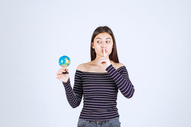 미니 글로브를 들고 침묵을 요구하는 스트라이프 셔츠에 젊은 여자