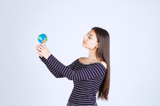 Молодая женщина в полосатой рубашке держит мини-глобус и выглядит взволнованной