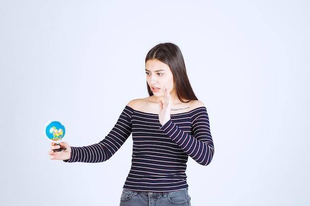Молодая женщина в полосатой рубашке держит мини-глобус и хочет его остановить