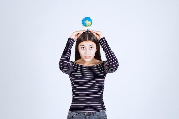 Молодая женщина в полосатой рубашке держит в руках мини-глобус