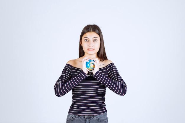 그녀의 손 사이에 미니 글로브를 들고 스트라이프 셔츠에 젊은 여자