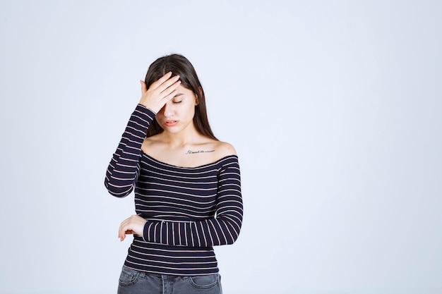 Молодая женщина в полосатой рубашке держится за голову из-за головной боли