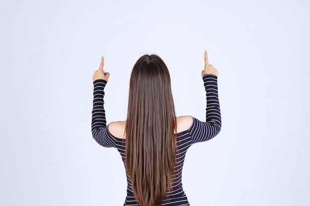 뭔가 뒤에 가리키는 스트라이프 셔츠에 젊은 여자