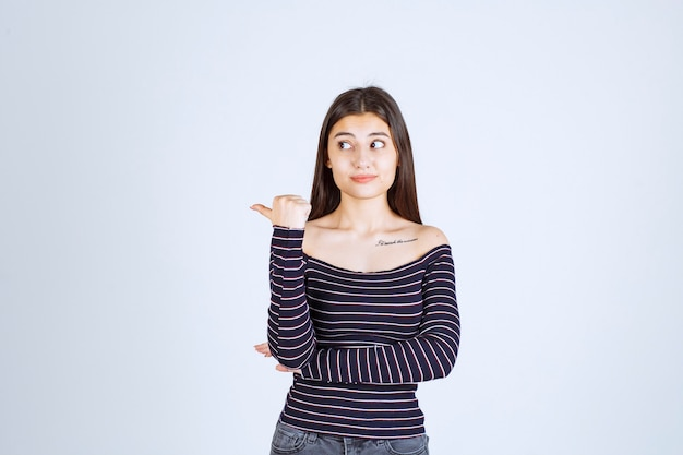 後ろの何かを指している縞模様のシャツの若い女性