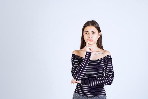 彼女のあごに手を置いて考えている縞模様のシャツの若い女性