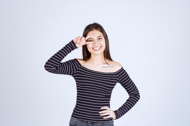 평화 기호를 보내는 스트라이프 셔츠에 젊은 여자