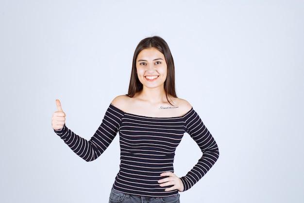 즐거움 손 기호를 보여주는 스트라이프 셔츠에 젊은 여자
