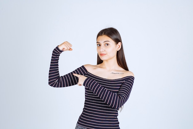 Молодая женщина в полосатой рубашке показывает мышцы руки и кулак