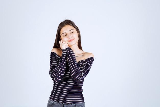 ストライプのシャツを着た若い女性が手を合わせて素敵なポーズを与える