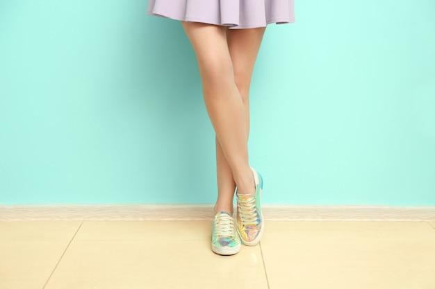 Молодая женщина в стильной повседневной обуви возле цветной стены