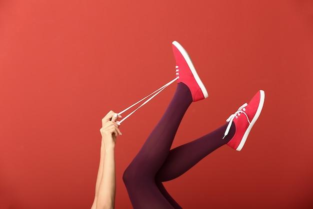色のスタイリッシュな靴の若い女性