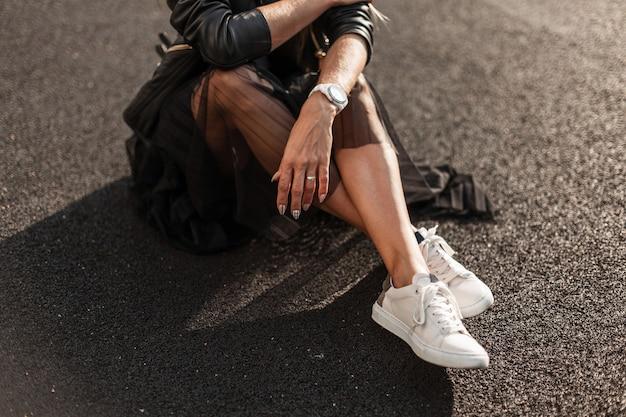 트렌디 한 가죽 블랙 스커트에 빈티지 블랙 스커트에 세련된 흰색 스니커즈에 젊은 여자는 화창한 날에 아스팔트에 앉아있다. 청소년 여성 의류의 세련된 가을 컬렉션. 확대.
