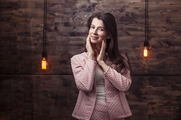 バックグラウンドで光るライトと自信を持ってビジネスを笑顔のスーツの若い女性
