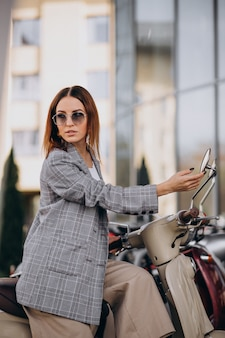 Young woman in suit standing by the scooter