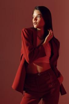 スーツを着た若い女性、カラーライト付きのスタジオ写真、女の子のファッショナブルなスタジオ垂直写真。高品質の写真