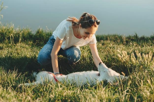 Hunkers에 잔디에 앉아 배경에 물과 함께 석양 근처에 누워 흰 강아지의 배를 문지르고 여름 옷에 젊은 여자