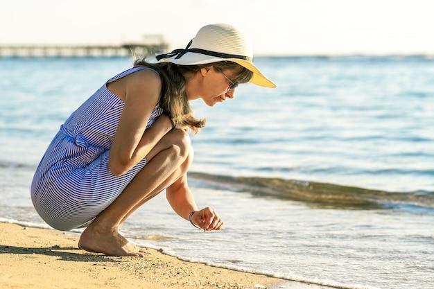 海のビーチの砂の上に何かを書く夏服の若い女性