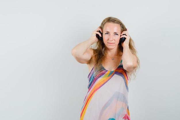 Молодая женщина в летнем платье слушает музыку в наушниках