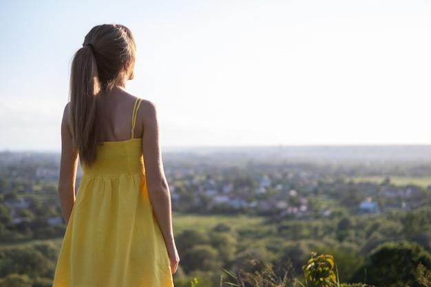 Молодая женщина в летнем платье стоя на открытом воздухе, наслаждаясь теплым днем.