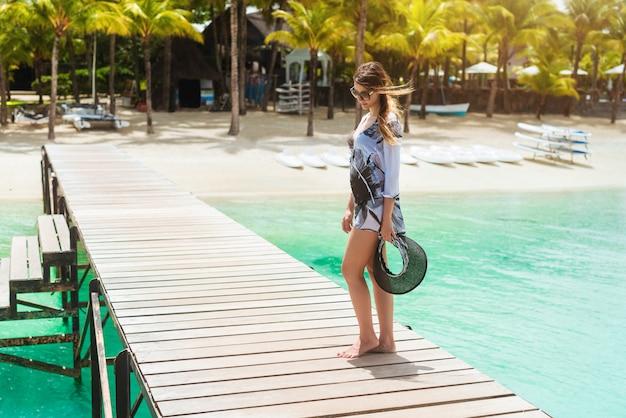 Молодая женщина в летнем платье, оставаясь на пирсе, глядя вниз
