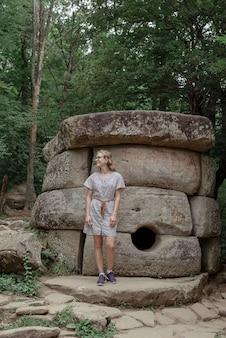 Молодая женщина в летнем платье гуляет возле большого дольмена в лесу