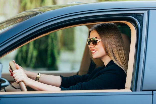 Молодая женщина в солнцезащитных очках за рулем