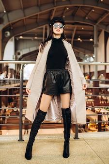 Молодая женщина в солнцезащитных очках, черной кожаной кепке и сером пальто