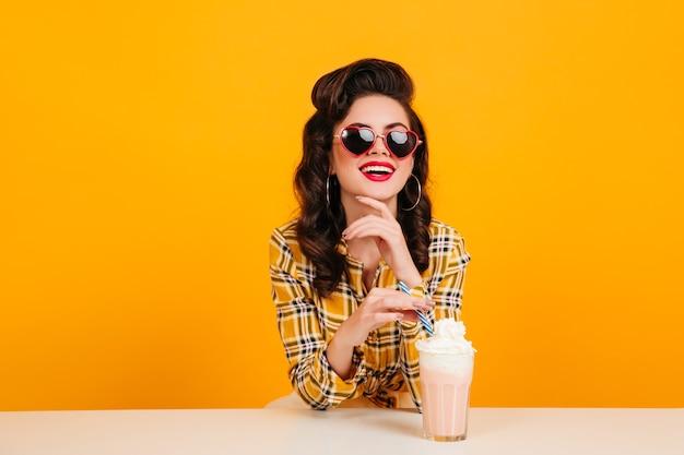 밀크 쉐이크를 마시는 선글라스에 젊은 여자. 노란색 배경에 고립 된 핀 업 레이디의 스튜디오 샷.
