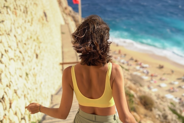暑い夏の日を楽しんでいるビーチでの休暇で素晴らしい気分でサングラスをかけた若い女性