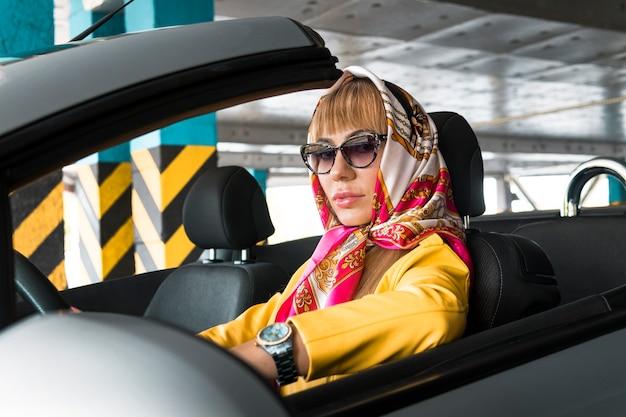 サングラスをかけた若い女性、コンバーチブル車を運転するスカーフ。ショッピングセンターモールの金髪ファッションモデル屋内地下駐車場。カブリオレでファッショナブルでスタイリッシュでリッチな成功した女性。