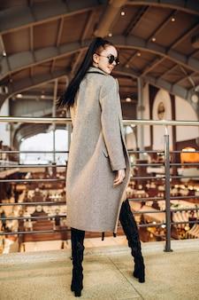Молодая женщина в солнечных очках, длинных сапогах и сером пальто