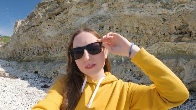 선글라스를 쓴 젊은 여성은 자연 속에서 셀카를 만든다. 한 여성이 바위를 배경으로 자신을 촬영하고 있습니다. 여행 및 야외 활동 개념입니다. 4k uhd