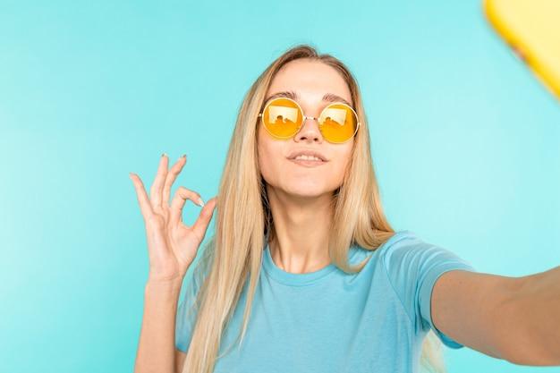 선글라스에 젊은 여자는 selfie를 만든다. 행복 한 젊은 아가씨는 확인 서명 하 고 미소 짓는다.