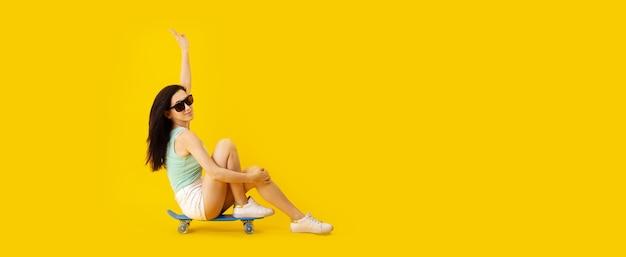 黄色いスペースの上のスケートボードに座っているサングラスの若い女性