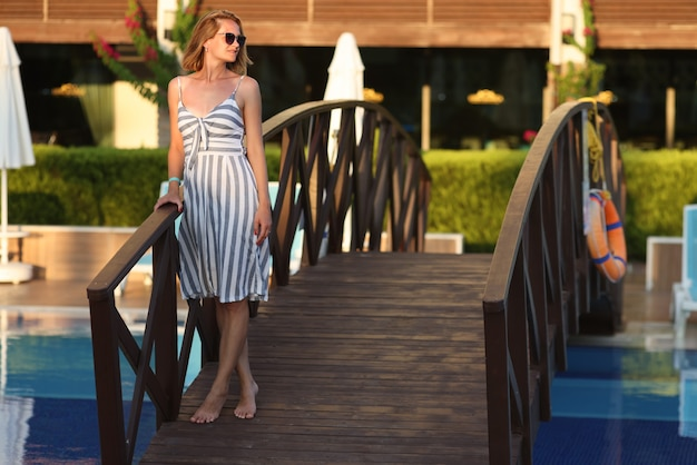 Молодая женщина в солнцезащитных очках, стоя на деревянном мосту