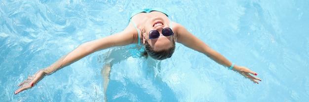 Молодая женщина в солнцезащитных очках, плавание в бассейне, вид сверху