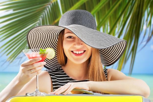 Молодая женщина в шляпе от солнца пьет коктейль