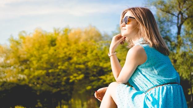 日当たりの良い庭の若い女性。屋外の夏の日。瞑想と自由の概念