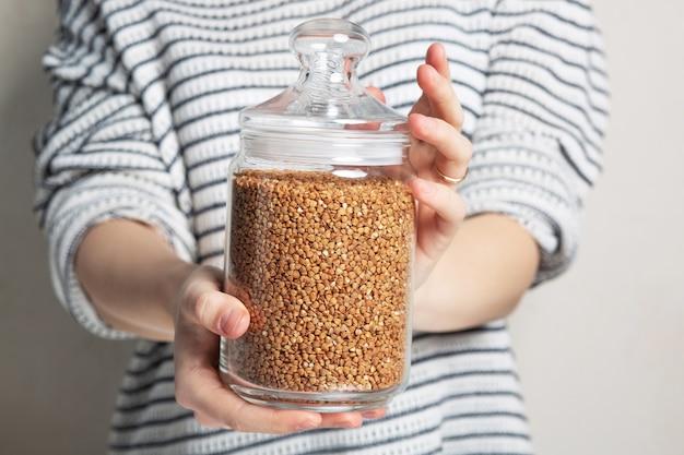 白い壁に保管するためにガラスの瓶にそばを保持しているセーターの若い女性。クローズアップショット