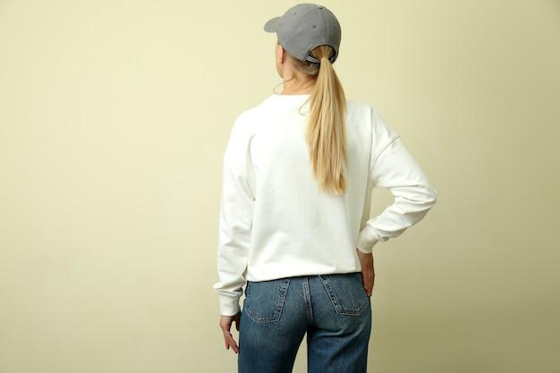 ベージュの背景にスウェットシャツとキャップの若い女性
