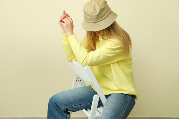 ベージュの表面に座っているスウェットシャツとキャップの若い女性