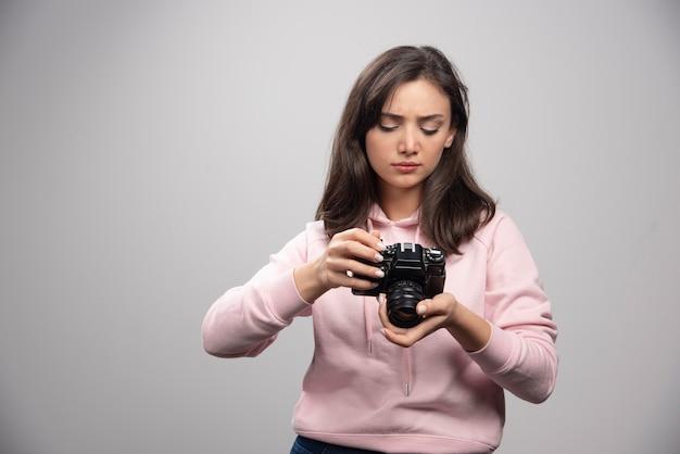 カメラを見ているスウェットシャツの若い女性。