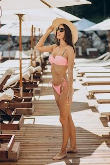 Молодая женщина в купальнике у бассейна
