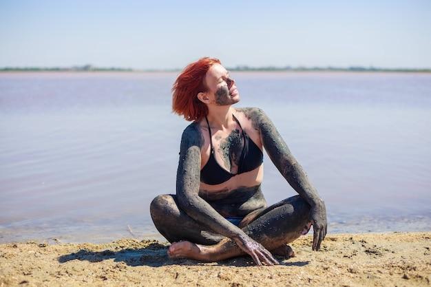 水着姿の若い女性は、塩漬けの湖から供給された顔と体に天然ミネラル泥を取っています