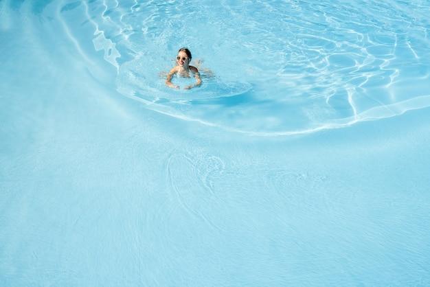 青い水と盆地で泳いで水着の若い女性。上からの概観