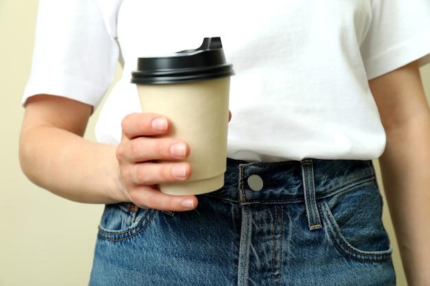 Молодая женщина в футболке держит бумажный стаканчик на бежевом фоне